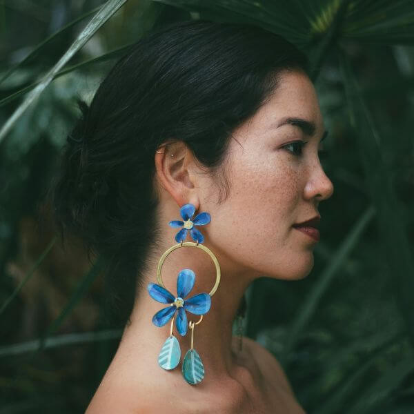 Woman wearing samoa earrings made in the shape of brightly coloured blue flowers