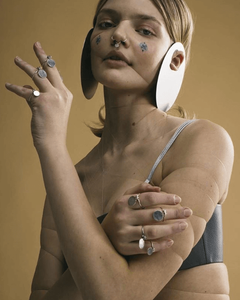 woman wearing large discs that hang from the ears, also with nose ring and tight string that pinches her face