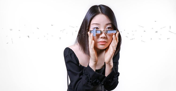Girl looking through handmade reading glasses