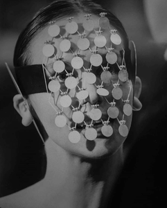 fashion model wearing mask made of tiny discs hinged together