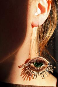 woman wearing a beaded earring in the shape of an eye