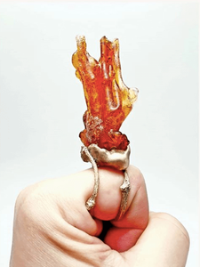 Ring from delight collection, bronze setting with large orange shaped resin flame shown on finger