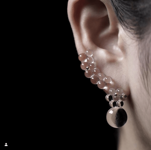 glass earrings on woman's ear, glass earrings are made of small circles attached together