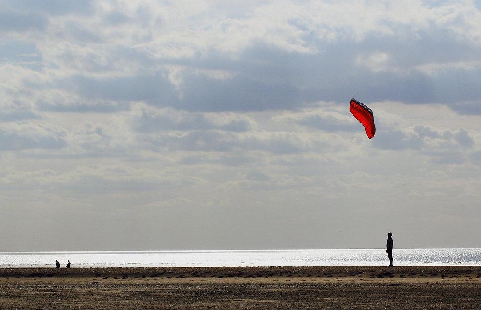 Like a Gormley installation, a solitary man observes a red kite on Old Hunstanton beach.jpeg