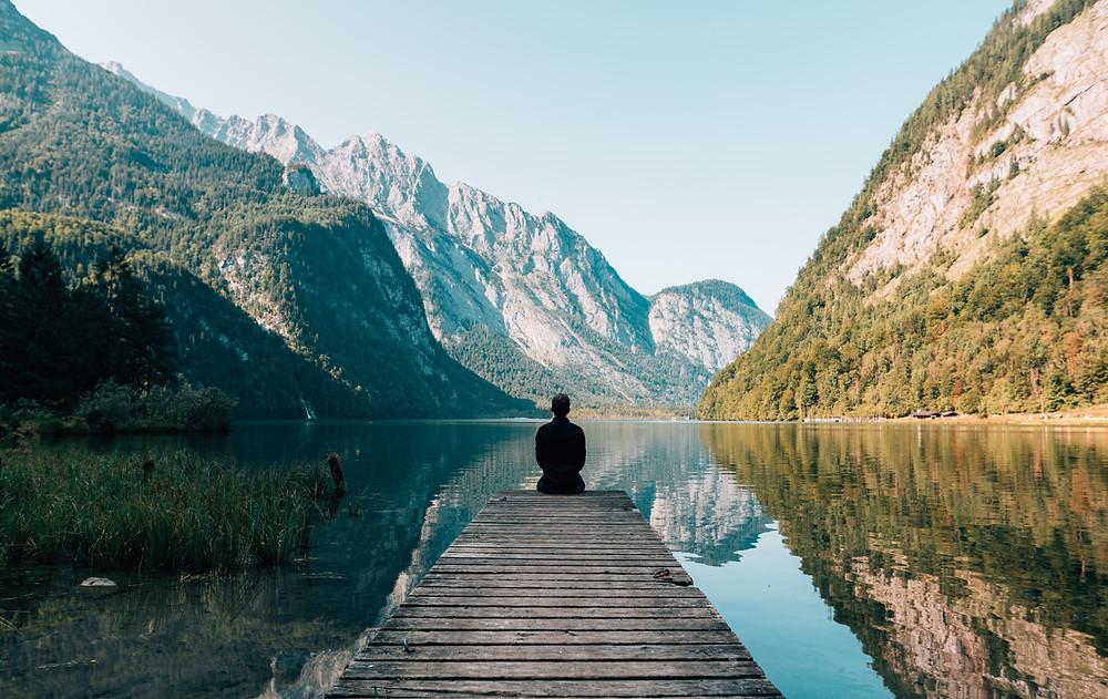 Man meditating at edge of bridge looking out at lake and mountains