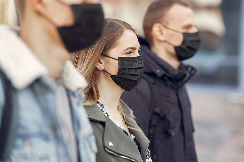 people standing in the street wearing face masks during lockdown