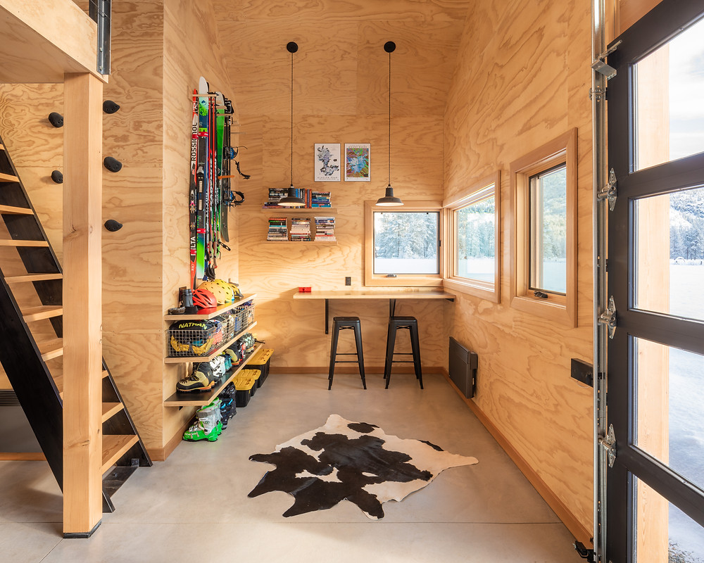 Room clad in plywood walls, work bench with black stools and black pendant lights, open shelving, ski gear, garage door, open loft, cow hide run. Johnston Architects brainstormed creative gear-storage solutions throughout the cabin, including a built-in shelf that doubles as a place to eat or do work, and a ski-waxing station. Image: Benjamin Drummond.