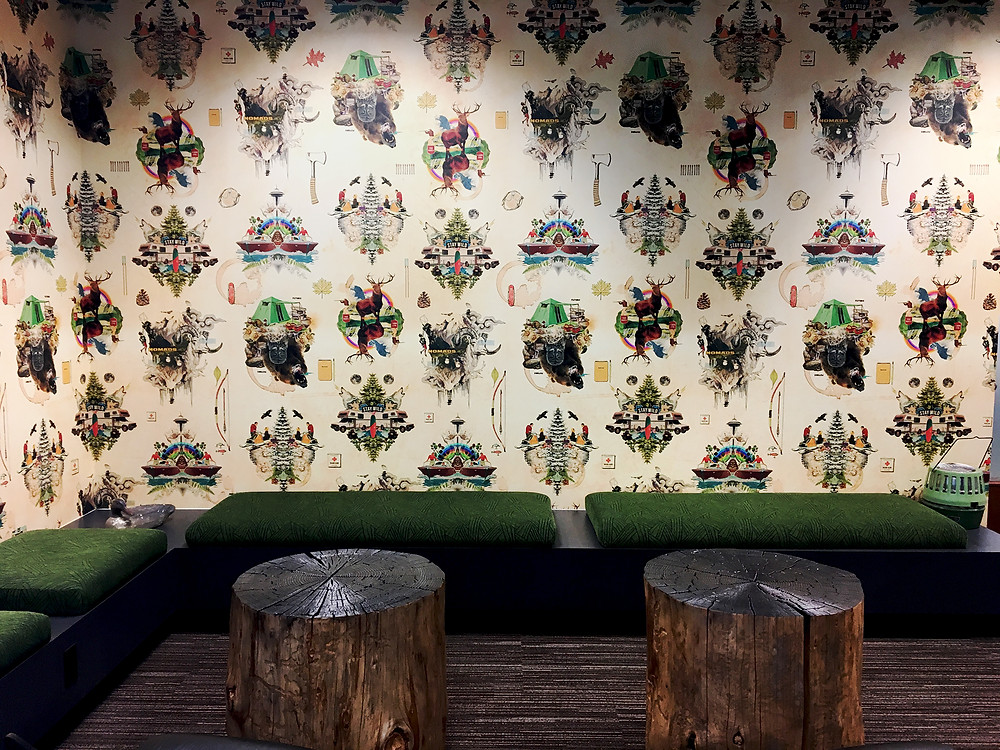 Custom wallpaper with illustrated graphics of Pacific Northwest and lifestyle and Seattle Space Needle, corner bench seating with forest green cushions, tree stump tables, gray carpet