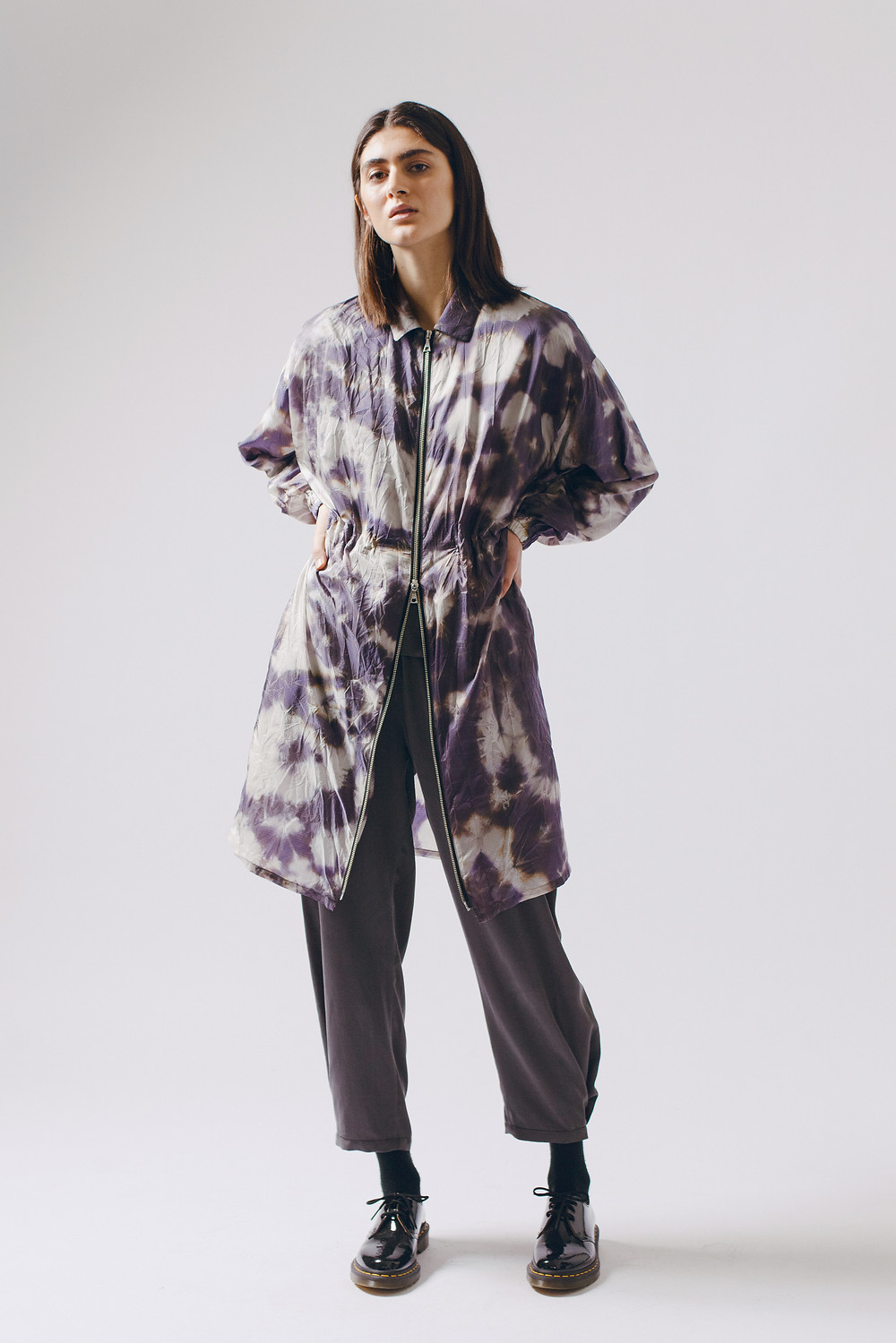 Maiden Noir, Seattle clothing brand, drops its A/W 2020 line, drawing colors, shapes, and relaxed silhouettes from the fascinating world of mycoflora. Model win purple tie die jacket with zipper, gray pants, black boots, long brown hairstyle.