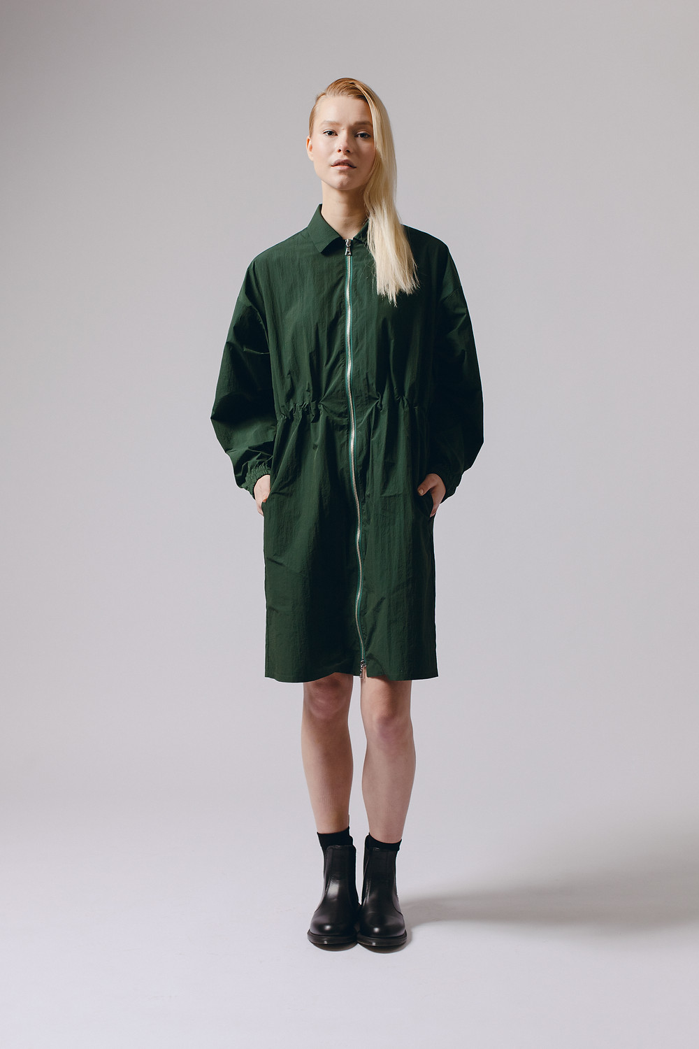 Maiden Noir, Seattle clothing brand, drops its A/W 2020 line, drawing colors, shapes, and relaxed silhouettes from the fascinating world of mycoflora, model in green dress, blonde hair, black boots