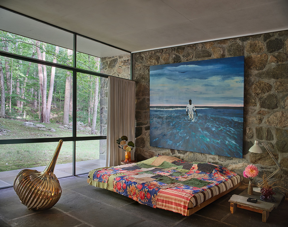 Midcentury modern bedroom with art, painting, glass window wall, rock wall, platform bed and art. At The Noyes House: Blum & Poe, Mendes Wood DM and Object & Thing. The Noyes House, New Canaan, Connecticut. Photo by Michael Biondo. Works pictured [left to right]: Alma Allen, Not Yet Titled (2020); Gaetano Pesce, Drip Vase (2020); Megumi Arai, Large bedspread (2020); Antonio Obá, Wade in the water II (2020); Frances Palmer, vase (2020); Gaetano Pesce, Tube Vase (2020).