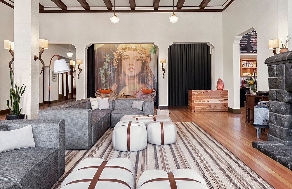 Redmond Hotel Oregon lobby with mural curtains, wall sconces, white and leather ottomans, gray sofas, hardwood floors, rustic and modern