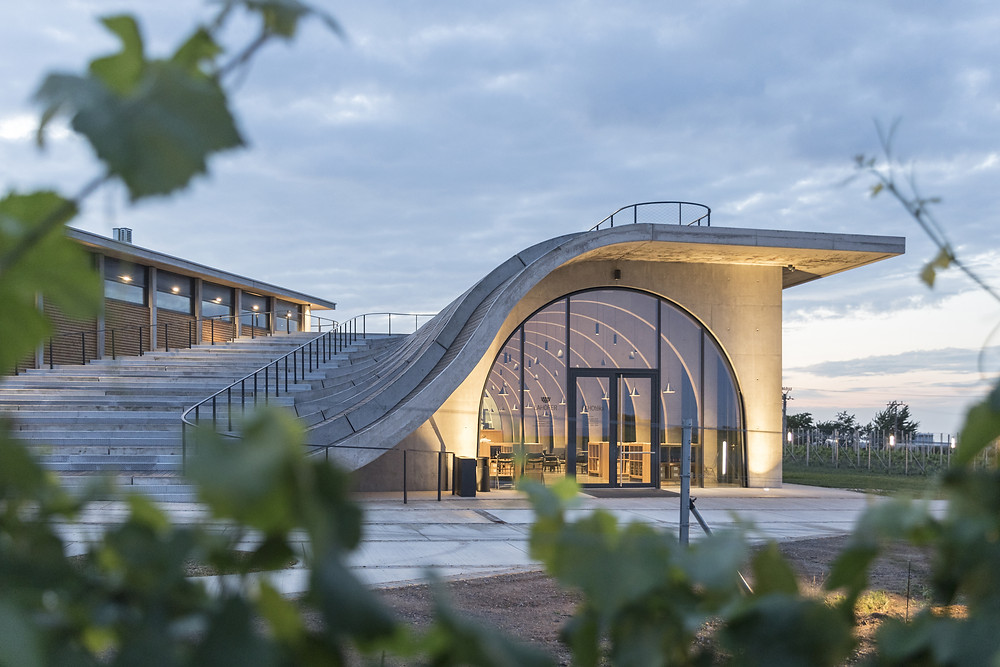 Concrete exterior with curved staircase that forms the curved roof over the Lahofer Winery tasting room spills into a large amphitheater.