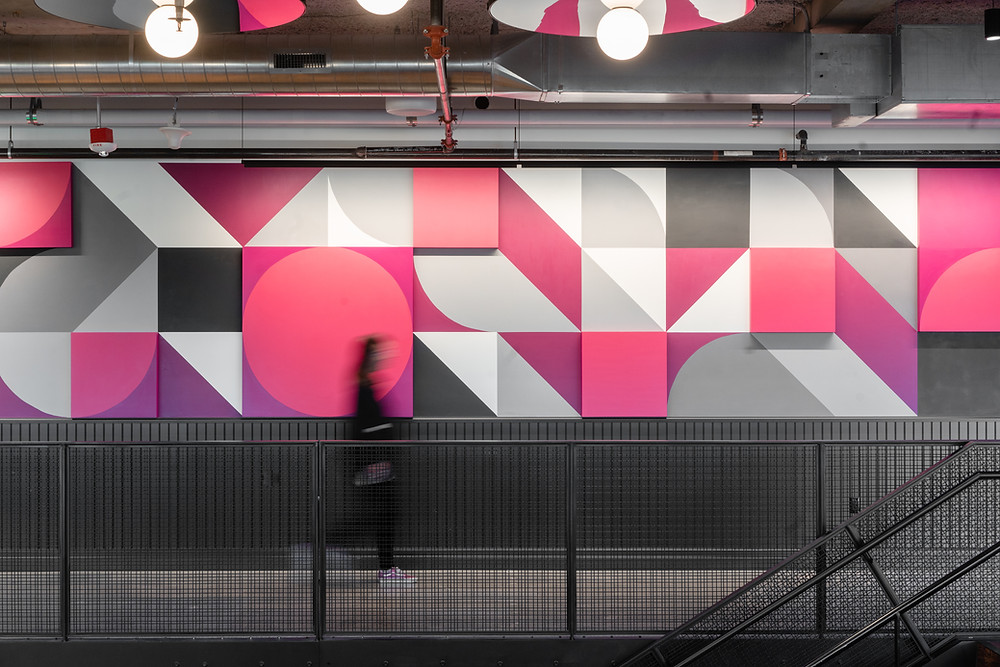 Blurry person walking in front of mural At T-Mobile's redesigned headquarters in Bellevue, Washington, a 45-foot-long mural by House of Sorcery incorporates the brand's signature bubblegum-pink color. Image courtesy of House of Sorcery.