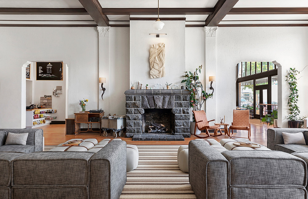 Redmond Hotel lobby with gray sofas striped rug, stone fireplace, woven leather rocking chairs, white walls exposed beams modern interior Oregon