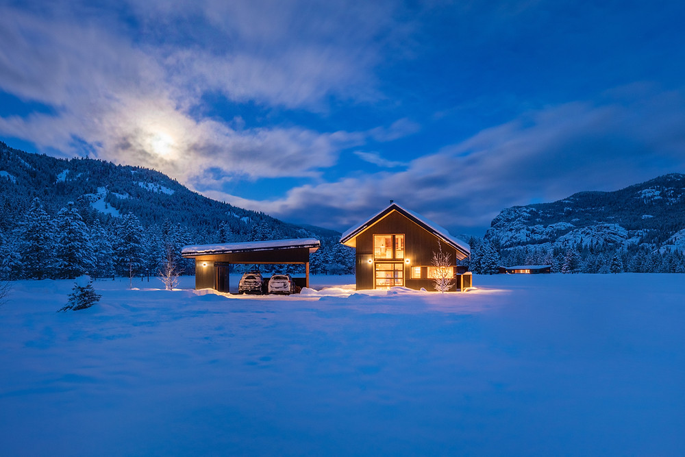 Cabin in the snow at dusk.   Johnston Architects designed this lofted cabin in Washington's Methow Valley around an outdoor-loving couple's collection of sporting gear. Image: Benjamin Drummond.