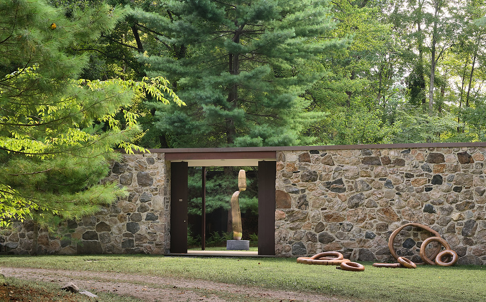 Exterior image of house in wooded setting. At The Noyes House: Blum & Poe, Mendes Wood DM, and Object & Thing. The Noyes House, New Canaan, Connecticut. Photo by Michael Biondo. Works pictured [left to right]: Alma Allen, Not Yet Titled (2020); Hugo França, Rings (2007).
