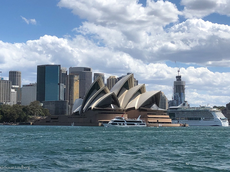 Sydney Harbor Opera House with boat and cruise ship and city scene behind view from across harbor