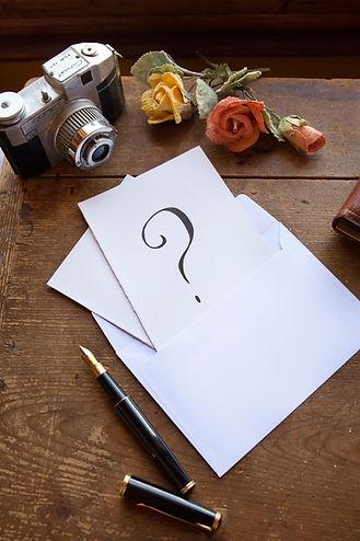 tavolo con sopra una lettera e un punto interrogativo