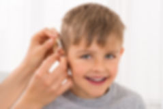 Close-up Of A Doctor Fitting Hearing Aid