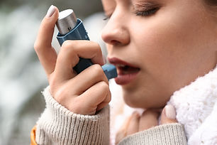 Young woman with inhaler having asthma a