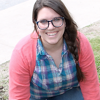 Rebecca Birtzu, Runner Up, a winner of 2016. Rebecca is smiling with a pair of glasses and a long braid in an outdoor space.