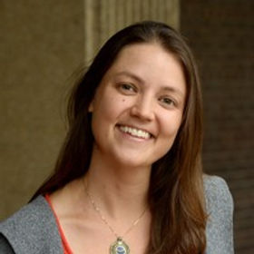 Haley Higdon, the Program Director of Natural Curiosity. Haley is smiling with brown long hair in front of a building.