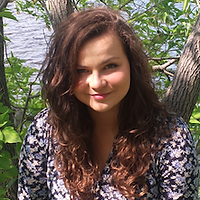 Aleksandra Pietraszn, a winner of 2015. Aleksandra is smiling with brown long curly hair in front of a tree and a lake.
