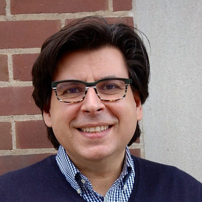 Richard Messina, the Principal of Natural Curiosity. He is smiling with short dark hair and a pair of glasses