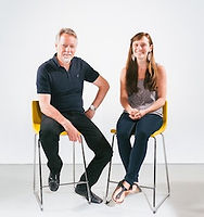 Ellie Clin, the Grand Prize Winner of 2016. Ellie is sitting in a yellow chair next to another person in front of a white background.
