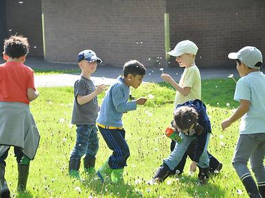 Children blowing dandelion seeds in a school yard.