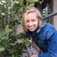 Janna Barkman, Runner Up, a winner of 2018. Janna is smiling with short silver hair next to some plants in front of a house.