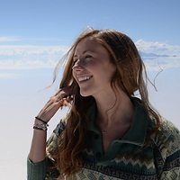 Jessie Sawyer, a winner of 2017. Jessie is smiling with long curly hair in front of a light blue cloud-like background.