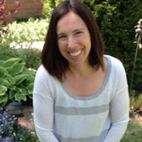 Joanne Arcand, Runner Up, a winner of 2015. Joanne is smiling with short hair in an outdoor space with lots of plants.