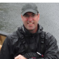 Mike Bibby, Runner Up, a winner of 2012. Mike is smiling with a grey hat and a black jacket in front of a lake.