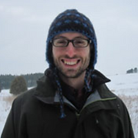 Paul Tucker, a winner of 2013. Paul is smiling with a hat and in a dark jacket in front of a snow field.