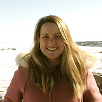 Leslie Campbell, a winner of 2016. Leslie is smiling with long blond hair in a red jacket in front of a lake.