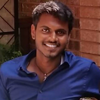 Luxshan Ambi, a winner of 2017. Luxshan is smiling with short dark hair and in a blue shirt in front of a building.