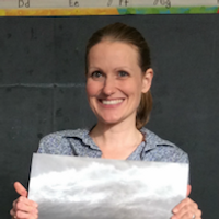 Jennifer Venalainen, Runner Up, a winner of 2015. Jennifer is smiling in a grey shirt with a picture in front of them.