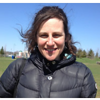 Marcia McVean, Runner Up, a winner of 2013. Marcia is smiling with long curly hair and in a jacket on a field.