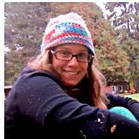 Petra Eperjesi, the Grand Prize Winner of 2014. Petra is smiling with a colourful hat and a pair of glasses in an outdoor space.