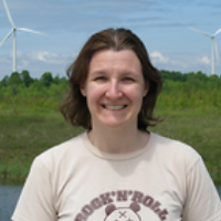 Heather Wilcox, a winner of 2010. Heather is smiling with brown short hair in a white shirt on a green field.