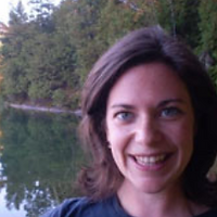 Stephanie Goom, a winner of 2014. Stephanie is smiling with dark short curly hair in front of a lake.