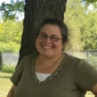 Barbara Myers, Runner Up, a winner of 2018. Barbara is smiling with a pair of glasses and a green shirt, standing in front of a tree.
