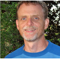 Stephen Skoutajan, the Grand Prize Winner of 2012. Stephen is smiling with a blue shirt and grey beard in front of a background of green plants.