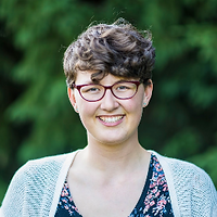 Erin Hartmans, the Grand Prize Winner of 2018. Erin is smiling with a pair of glasses and curly short hair in front of a green background.
