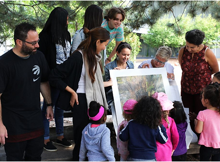 A person with dark hair tied back showing a picture to people in an outdoor space with trees.