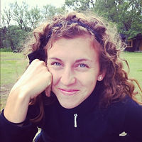 Rachel Shiderman, a winner of 2016. Rachel is smiling with brown curly long hair and a dark sweater in front of an outdoor green space.