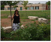 Gail Blackman, Runner Up, a winner of 2011. Gail is standing next to a small tree and some plants, and in front of some buildings in an outdoor space.