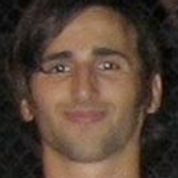 Amir Lewin, a winner of 2010. Amir is smiling with dark short hair in front of a dark background.